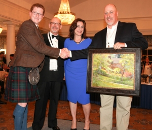 "Justin Critz presents the Druid Hills Civic Association's ""Best Use of Light"" Award to painter Chuck Marshall at the awards soiree at the Druid Hills Golf Club. Andy Hall and Lillian Ansley stand between them."